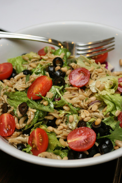 Wholemeal pasta salad with olives, tomatoes and pine nuts