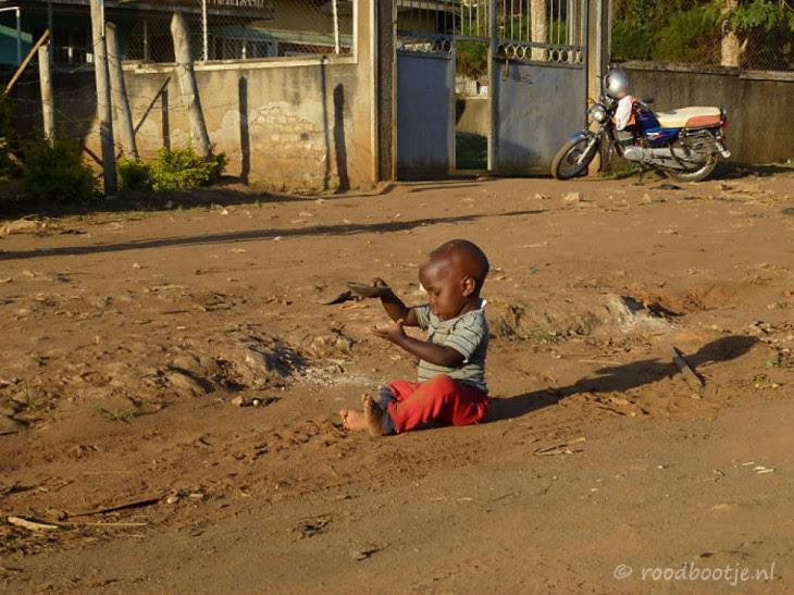 Niño jugando con arena en Uganda