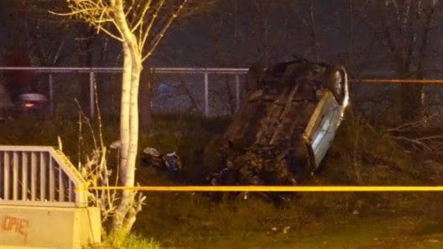 La voiture de taxi volée et accidentée repose sur le toit en bordure de la rue.