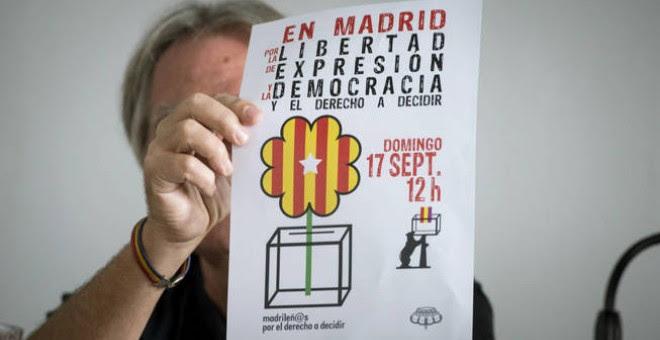 Un activista muestra el cartel del acto de 'Madrileños por el derecho a decidir', en una rueda de prensa este miércoles. EFE