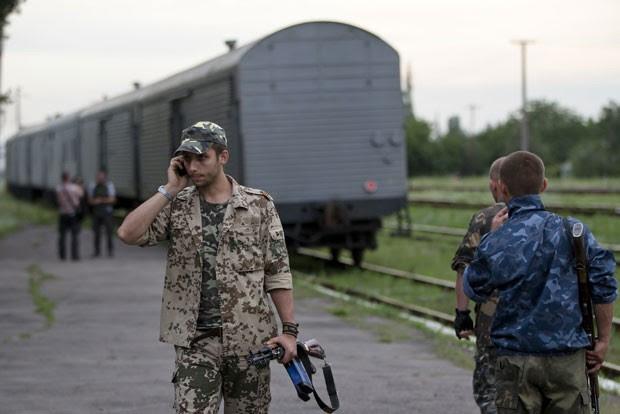 Rebelde das forças pró-Rússia fala ao telefone enquanto trem com corpos deixa estação em Torez, na Ucrânia (Foto: Vadim Ghirda/AP)