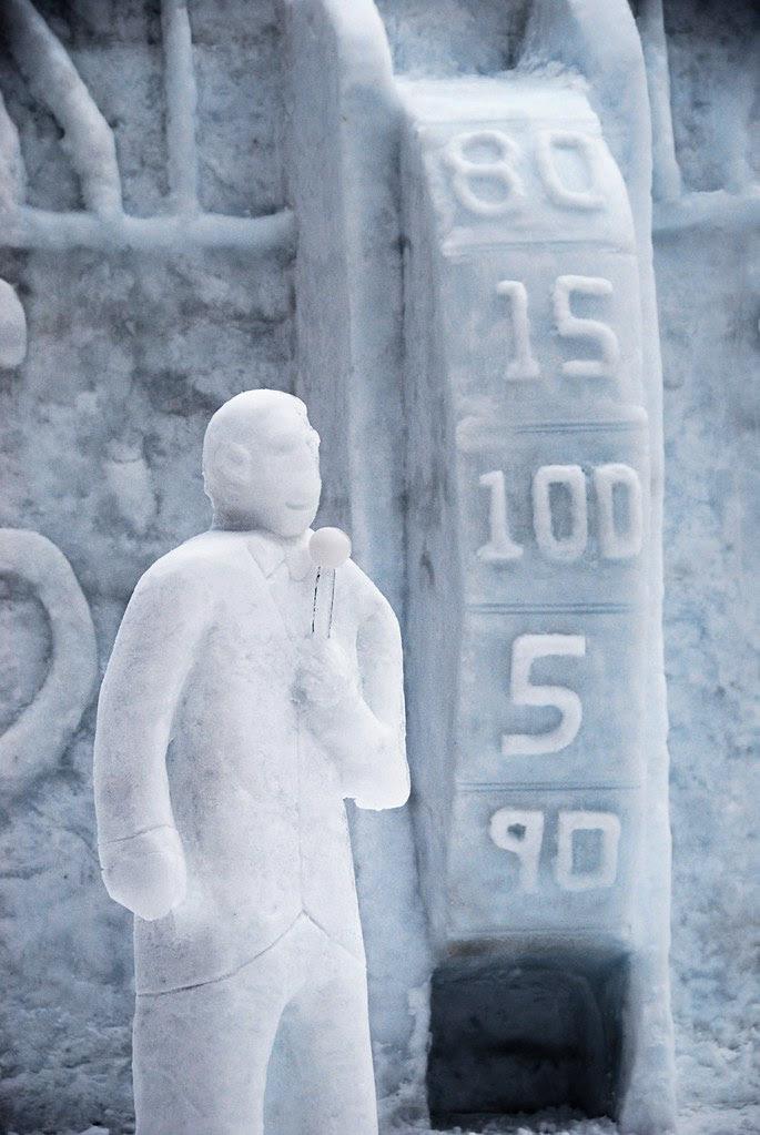 A snow statue of Bob Barker with the Price Is Right Showcase Showdown wheel.
