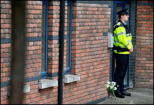 Flowers left as Gardai preserve the scene at the Riverside apartment at Poddle Park in Kimmage where the young child was stabbed to death. Pic Steve Humphreys