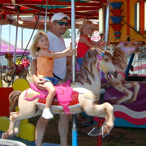Dad and his girls enjoying the merry-go-round.