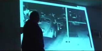 """At a press conference in Philadelphia Dec. 4, 2007, Hans Bennett shows slides of the Pedro Polakoff crime scene photos. This one, known as """"The Moving Hat,"""" shows Officer Faulkner's hat on the top of Billy Cook's VW. For the official police photo, it had been placed on the sidewalk. – Photo: Journalists for Mumia video"""