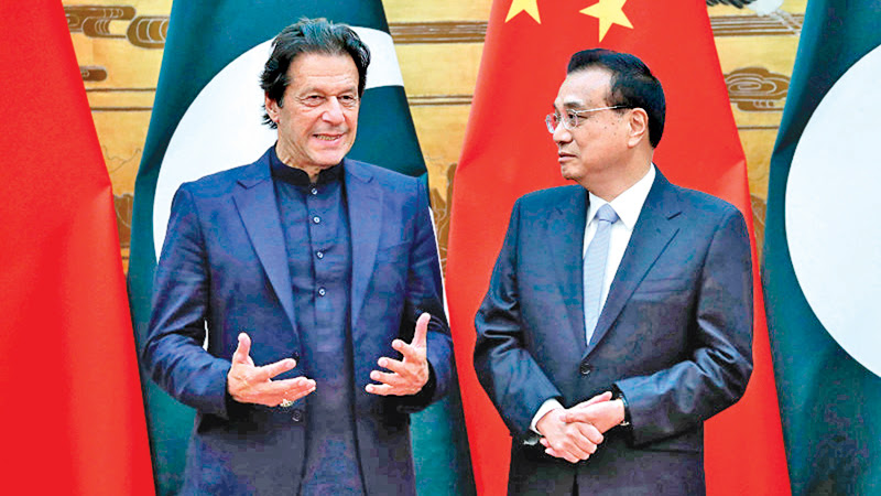 Pakistani Prime Minister Imran Khan speaks with Chinese Premier Li Keqiang during a signing ceremony on October 8 in Beijing.