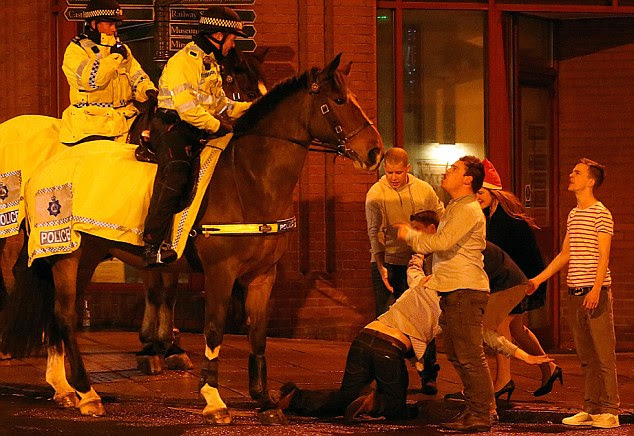 A group of revelers look dwarfed by the giant Police horses on their 'Mad Friday' night out in York