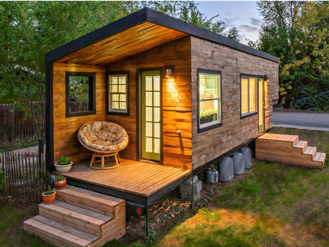 This 196-square-foot house near Boise, Idaho, is home to Macy Miller, her partner James, their daughter Hazel, and their Great Dane, Denver. A 27-year-old architect, Macy designed the home from scratch and built it on a 24-foot flatbed with help from friends and family. Clad in siding made of recycled pallet wood, the minimalist home is flooded with light and feels spacious despite its size. Hidden storage under the bed, above the pantry, and behind the fridge are contrasted with open shelving in the kitchen to make the space feel bigger. In total, Macy spent about $11,000 on her tiny house and is now able to live rent- and mortgage-free. —Ellen Sturm Niz Look inside Macy's tiny house.