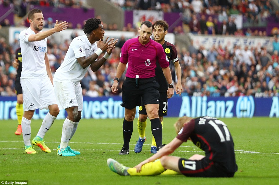 Leroy Fer of Swansea City argues with Niel Swarbrick after he awarded a penalty after a foul on Kevin De Bruyne