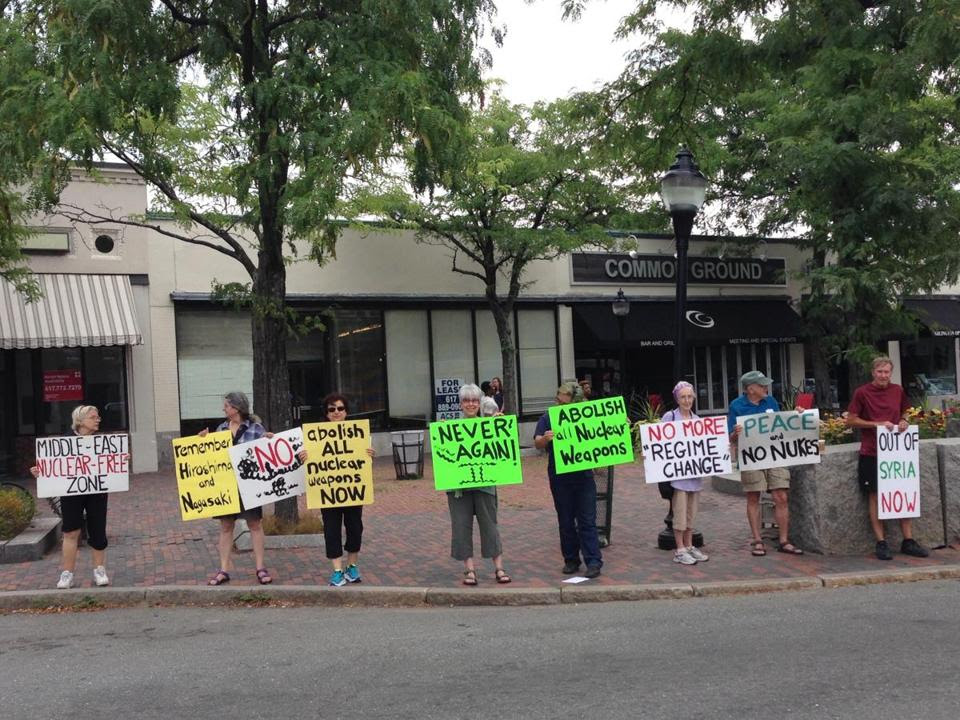 Members of the Arlington chapter of United for Justice with Peace hold signs in Arlington Center in protest of nuclear weapons on Massachusetts Avenue.