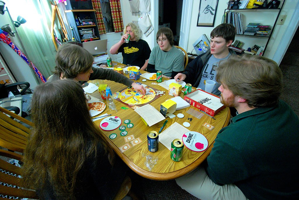 A wide view of a table of people playing a boardgame.