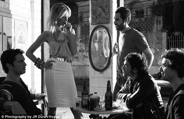Chamando a atenção: A supermodelo também é visto cercado por alguns homens muito atento, que admiram sua forma em uma saia lápis skintight branco, que é combinada com uma blusa sem mangas arco buceta