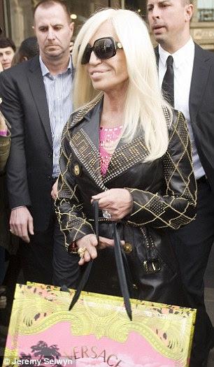 Donatella usava um vestido de couro rosa studded, que ela tinha tomado para torná-lo um ajuste mais apertado, e uma jaqueta de couro, ambos da coleção