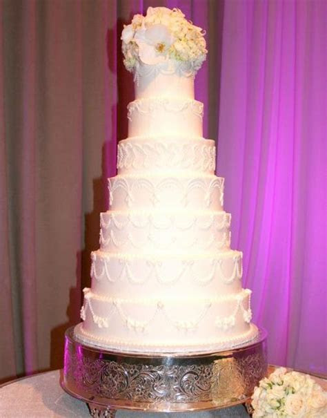 Seven tier white wedding cake with white rose flower
