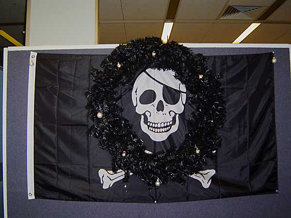 black christmas wreath, with baubles, with jolly roger peeking through the hole
