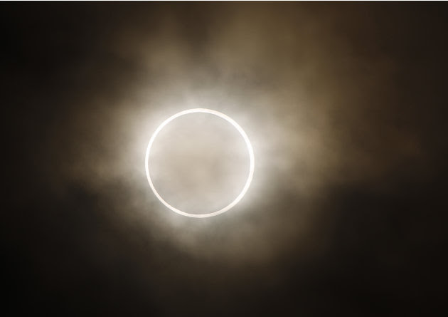 An annular eclipse appears at a waterfront park in Yokohama, near Tokyo, Monday, May 21, 2012. The annular eclipse, in which the moon passes in front of the sun leaving only a golden ring around its e