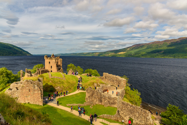 Inverness, Scotland  - August 10, 2017: View of Urquhart Castle in Scotland with a row of visitors exploring castle ruins.