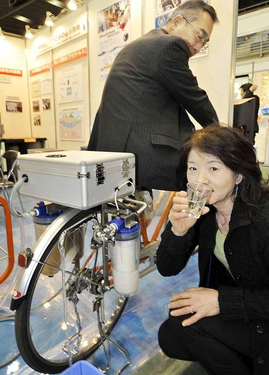 Expositora de feira de tecnologia sustentável, no Japão, mostra bicicleta que produz água filtrada