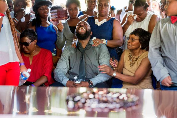 Michael Brown Sr. yells out as the casket is lowered during the funeral service for his son Michael Brown in Normandy, Mo., Monday, Aug. 25, 2014. Hundreds of people gathered to say goodbye to Michael Brown, the 18-year-old shot and killed Aug. 9 in a confrontation with a police officer that fueled almost two weeks of street protests.