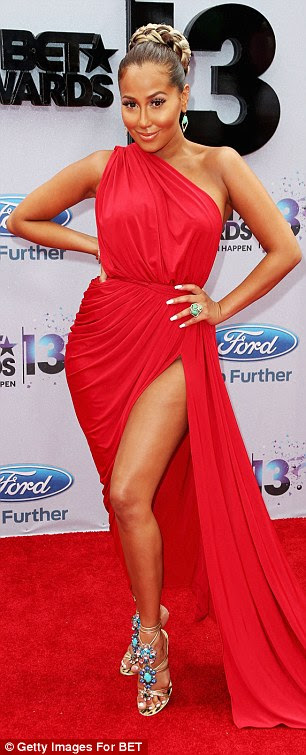 Ravishing in red: Singer Adrienne Bailon put her curves on display in a revealing Grecian gown