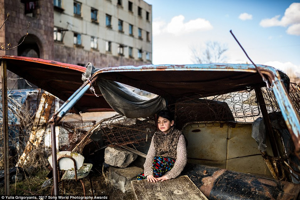 A nine-year-old girl called Syuzanna takes shelter in the shell of a dilapidated car outside the abandoned building she lives in, in Gymri, Armenia, where the poverty rate is 47 per cent
