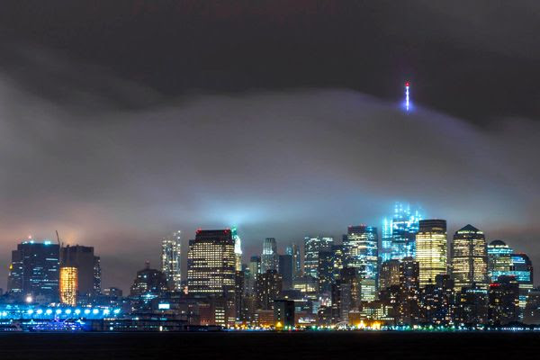 The 1 WTC's antenna spire is visible above a layer of fog that enshrouds New York City.