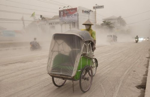 A man wears a mask as he rides a becak, a kind of rickshaw, on a road covered with from Mount Kelud,  in Yogyakarta