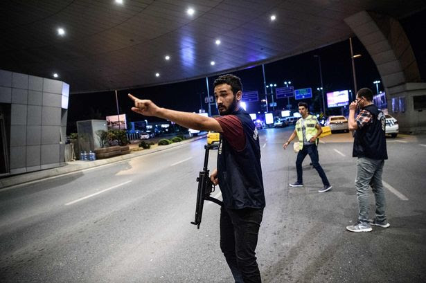 A Turkish police officer reacts at Ataturk airport`s main gate