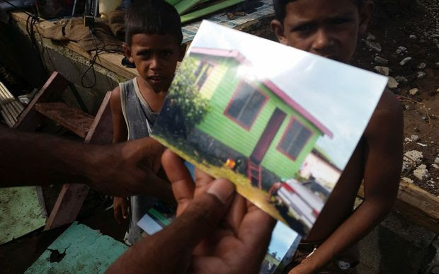 Mohammed Nadim shows photos of the house that was destroyed by Winston.