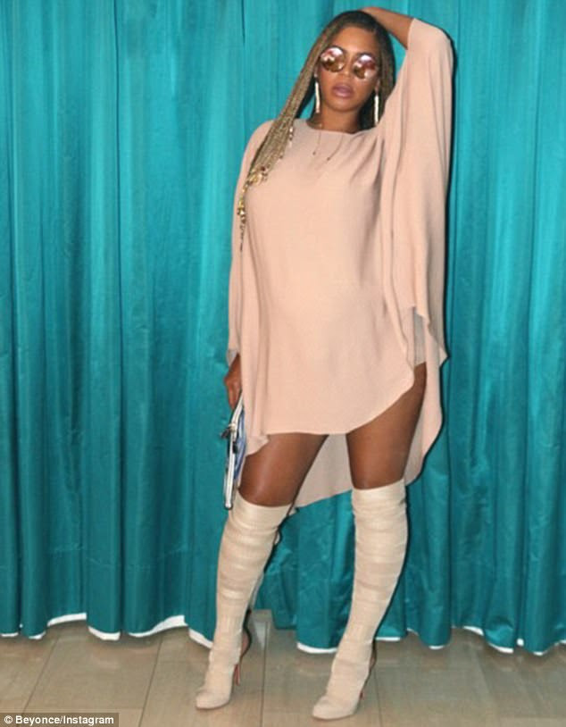 Stunner:The 35-year-old flashed her thighs in the neutral draped mini, adding thigh-high boots and tinted sunglasses