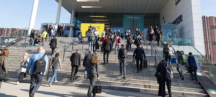 People walk up the steps of an exhibition hall to photokina