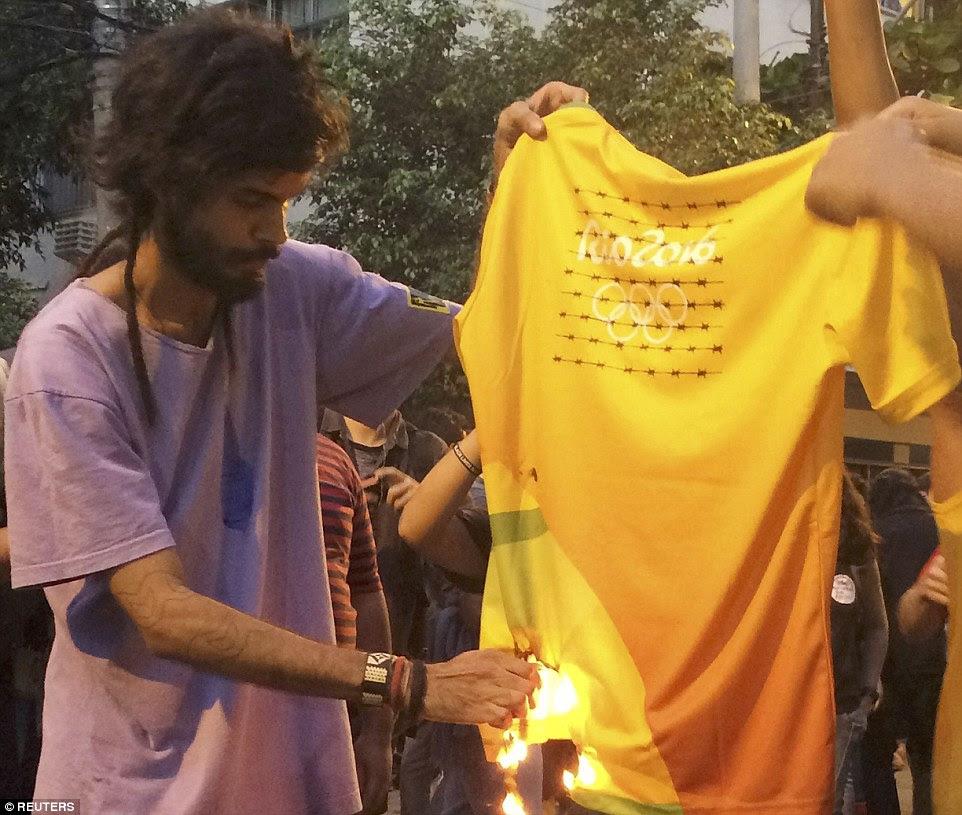 Um manifestante foi retratado colocando fogo em um t-shirt olímpico durante um protesto perto do estádio do Maracanã