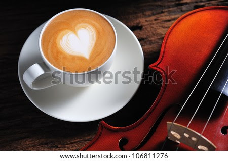 Latte art and violin on wooden table - stock photo