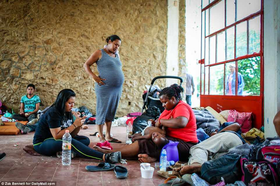 A woman changes her baby's diaper while others look on atthe Ferrocarrilero VÌctor F. Morales Sports Center in MatÌas Romero, Oaxaca, Mexico