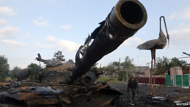Pro-Russian separatist walks past destroyed tank at Savur-Mohyla, east of the city of Donetsk. 28 Aug 2014