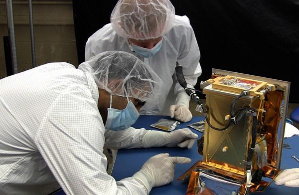 Two MIT students prepare the Regolith X-Ray Imaging Spectrometer instrument for flight aboard NASA's OSIRIS-REx spacecraft.