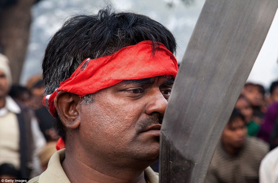 A devotee holds his traditional kukri knife before the beginning of the animal sacrifices