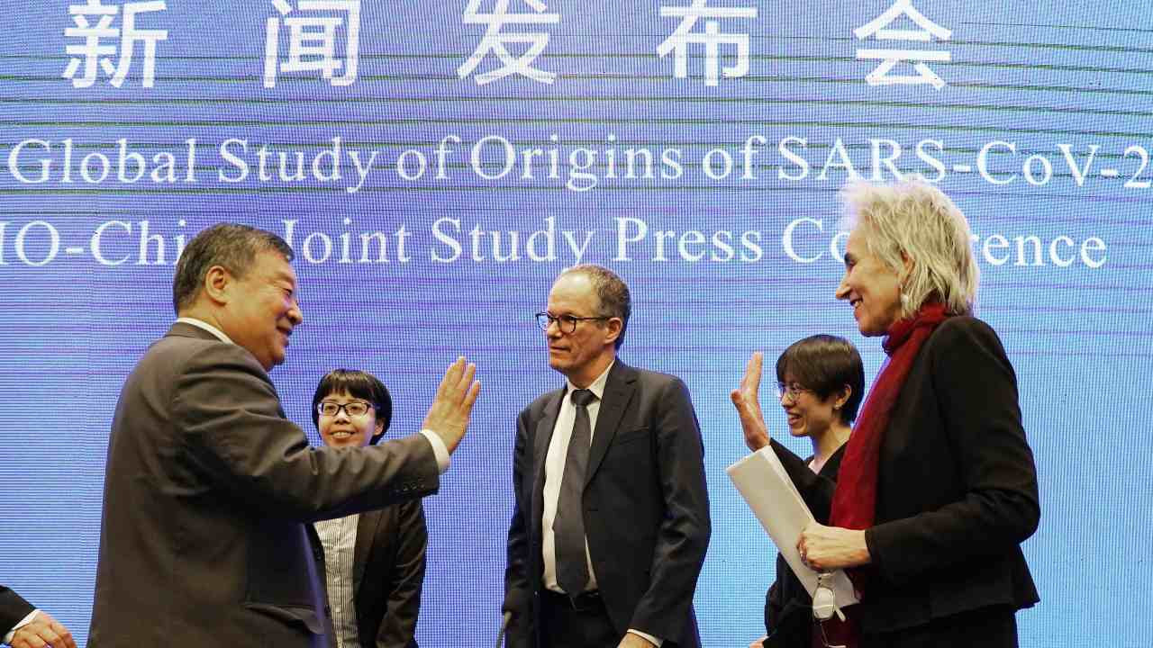 Members of the WHO team Marion Koopmans (R) and Peter Ben Embarek (C) say farewell to their Chinese counterpart Liang Wannian (L), after a WHO-China Joint Study Press Conference held at the end of the WHO mission in Wuhan, on 9 Feb 2021. AP