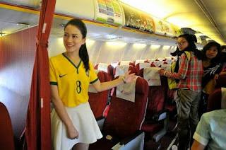 A flight attendant wearing a Brazil soccer team jersey welcomes passengers onto an airplan Pramugari Seksi Maskapai di Tiongkok Mengenakan Kaus Bola