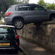 Unexplainable crash: Car left balanced on top of wall and Fiat 500