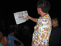 Song Lau reading newspaper article