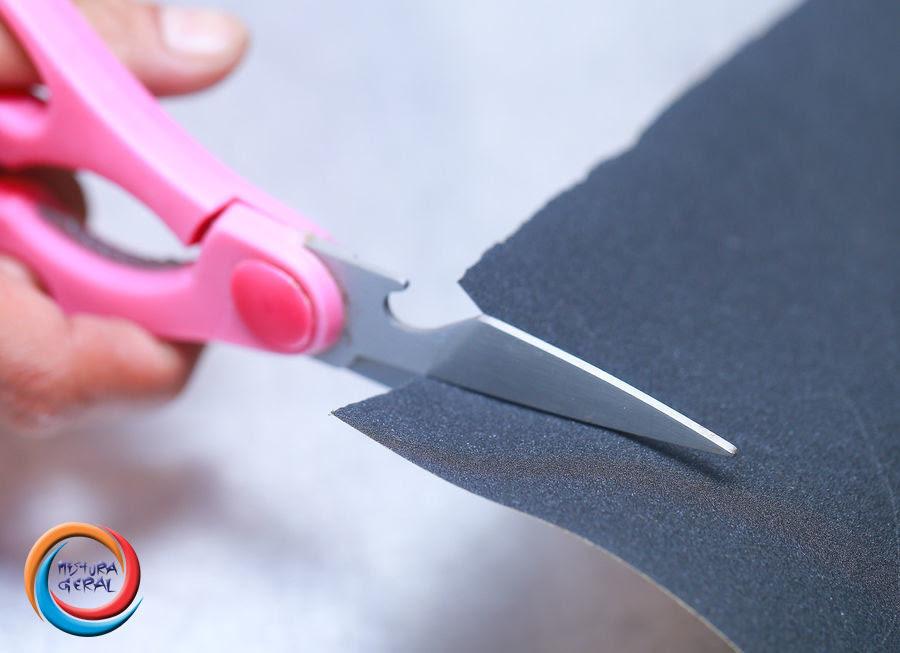 Amole tesouras cortando uma folha de lixa de papel.
