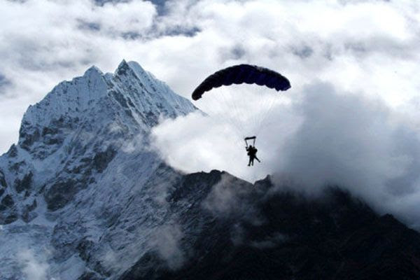 With Mt. Everest in the backdrop, the tandem skydivers are about to land at the drop zone located in the middle of the Himalaya Mountains.