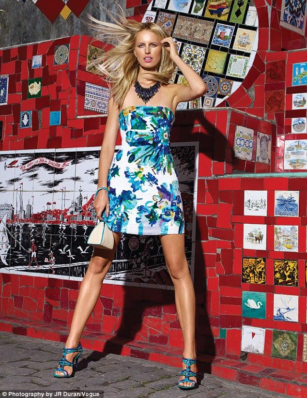 Vibrante: Outra foto mostra Karolina em uma bonita floral mini-vestido que ela posa na frente de uma parede de mosaico