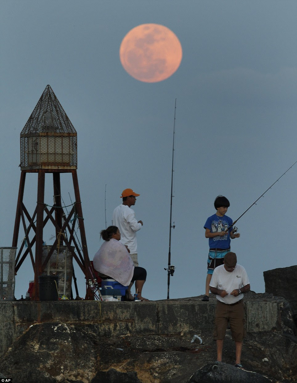Beacon: Fishermen near Bal Harbour in Florida rest on a jetty as the moon rises in the Atlantic Ocean