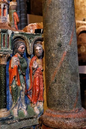 Un sensor de luminosidad, de color negro, sobre una de las figuras de piedra policromada del cenotafio de los santos, en la basílica de San Vicente.