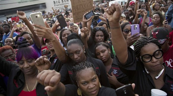 """Demonstrators mourned the loss of Alton Sterling, chanting """"black lives matter"""" and """"hands up don't shoot"""" [Bryn Stole/Reuters]"""