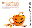 Halloween candy in orange cup with face - stock photo