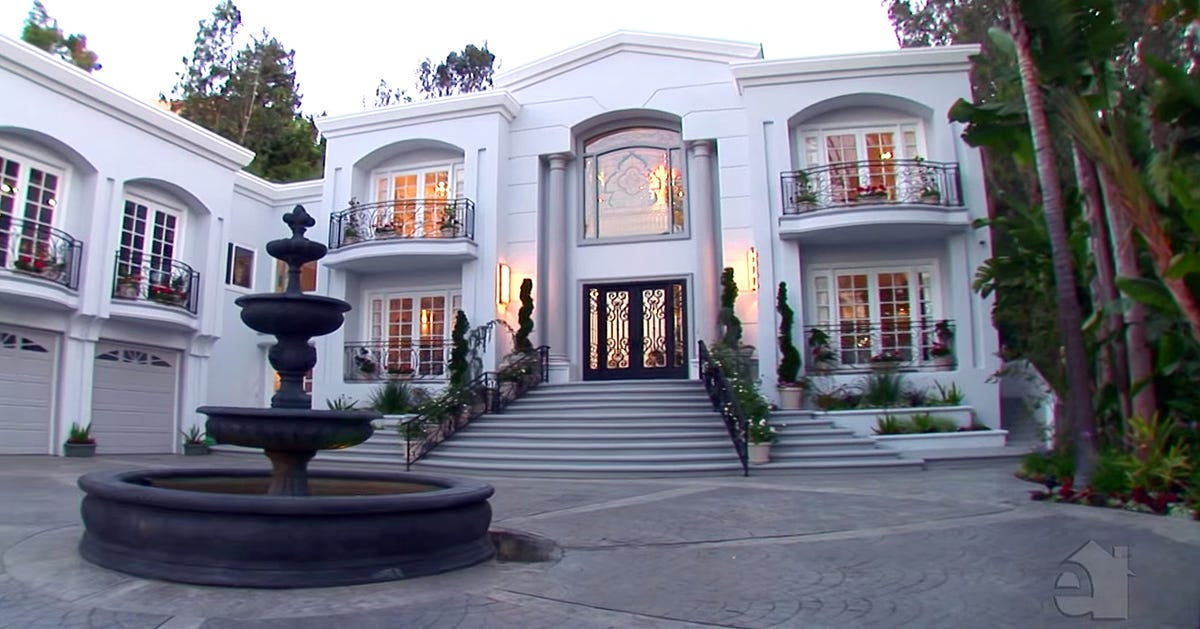 The entrance is two stories high with a fountain centered in the driveway.