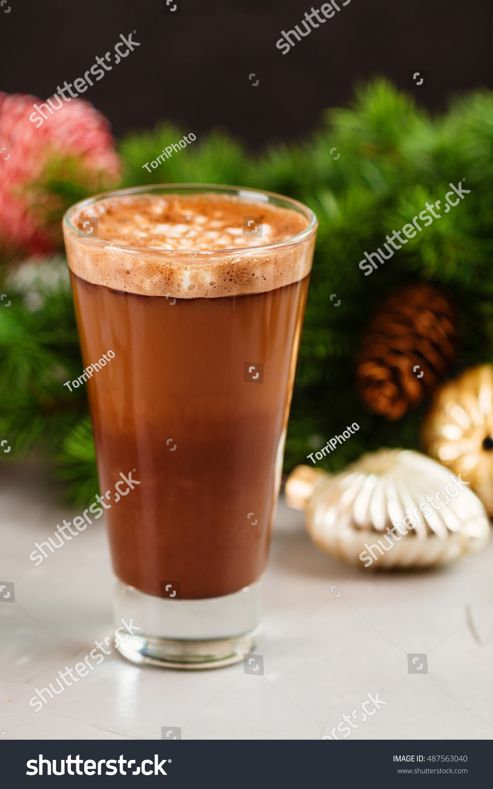 Hot chocolate with whipped cream in tall glass on Christmas background with decorations